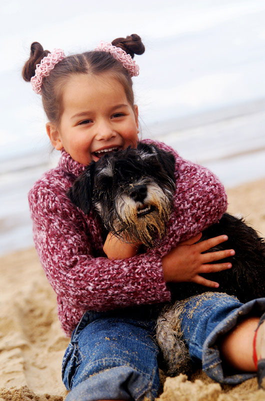Young girl holding the family dog on the beach