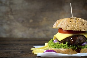 Juicy cheesburger on the wooden background