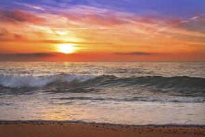 Colorful ocean beach sunrise with deep blue sky.