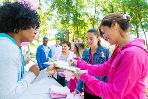 Diverse group of adults and teenagers are lined up at registration table in sunny park.