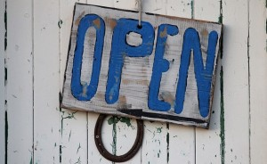 wooden sign that says open in blue paint