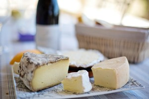 plate with various cheeses and a bottle of red wine